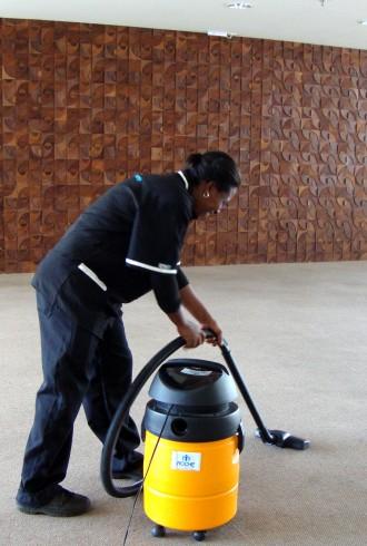 Funcionária Roche de serviços terceirizados de limpeza e conservação aspirando o chão