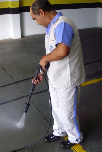 Funcionário Roche de serviços terceirizados de limpeza e conservação lavando o estacionamento